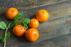Несколько апельсинов мандарина на деревянной предпосылке с мятой стоковые фото
