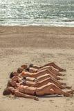 Несколько девушек в бикини лежа на песчаном пляже Стоковые Фотографии RF