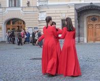 Несколько женщин в идентичных красных платьях говорят друг к другу собранный в круге Санкт-Петербург Лето 2017 Стоковое Изображение