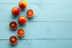 Несколько жизнерадостных апельсинов на голубой деревянной предпосылке Стоковые Изображения