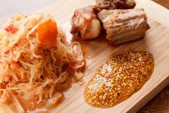 Несколько зажаренных в духовке нервюр свинины с томатом, морковами и капустой на разделочной доске Стоковые Фото