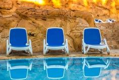 Несколько из loungers солнца красивым бассейном Стоковые Изображения