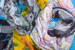 Несколько картин для шарфов и много цветов на таблице Стоковая Фотография