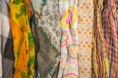 Несколько картин для шарфов и много цветов на таблице Стоковое Фото