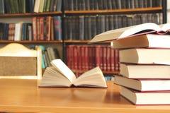 Несколько книг в таблице с предпосылкой книжных полок Стоковая Фотография