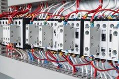 Несколько контакторов аранжировали в ряд в электрическом шкафе стоковые фотографии rf