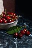Несколько красных сладостных вишни и больших зеленых лист на таблице Fres Стоковая Фотография RF