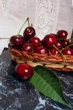 Несколько красных сладостных вишни и больших зеленых лист на таблице Fres Стоковая Фотография