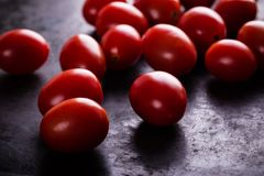 Несколько красных томатов вишни на черной доске Стоковое Изображение