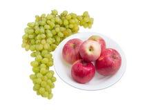 Несколько красных яблок на блюде и группе белых виноградин Стоковое Изображение