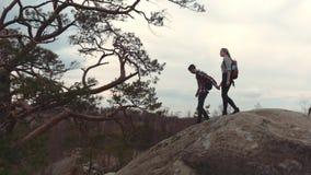 Несколько молодые любовники при рюкзаки держа их руки и взбираясь вниз максимум облицевали холм горы Туризм акции видеоматериалы