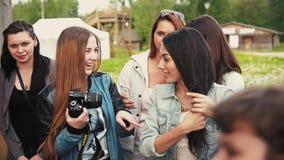 Несколько молодых привлекательных девушек с камерой в парке на фестивале лета день солнечный видеоматериал