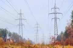 Несколько надземных линий электропередач среди осеннего леса Стоковые Изображения RF