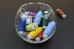 Несколько потоков в пластичной или стеклянной чашке Продевает нитку собрание в стеклянной чашке Стоковое фото RF