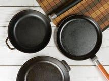 Несколько пустых сковород чугуна на белой деревянной предпосылке над взглядом Стоковые Изображения RF
