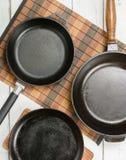 Несколько пустых сковород чугуна на белой деревянной предпосылке над взглядом Стоковое Изображение RF