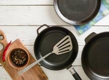 Несколько пустых сковород чугуна на белой деревянной предпосылке перцы смешивания в шаре Стоковое Изображение