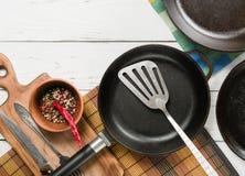 Несколько пустых сковород чугуна на белой деревянной предпосылке перцы смешивания в шаре Стоковые Фотографии RF