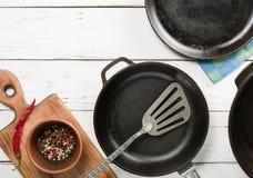 Несколько пустых сковород чугуна на белой деревянной предпосылке перцы смешивания в шаре Стоковая Фотография