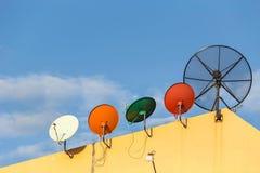 Нескольк спутниковая антенна-тарелка установленная на крышу дома с голубым небом Стоковые Фото
