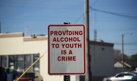 Несовершеннолетний выпивая предупредительный знак преступления алкоголя стоковое фото