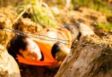 Несосредоточенный бегунов гонки грязи проходя под препоны колючей проволоки во время весьма гонки препоны, стоковое изображение