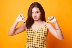 Несчастная азиатская выставка девушки thumbs вниз с обеими руками стоковая фотография