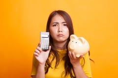 Несчастная азиатская женщина с калькулятором и копилкой в желтом dre стоковые изображения rf