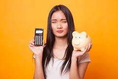 Несчастная азиатская женщина с калькулятором и копилкой стоковая фотография