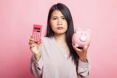 Несчастная азиатская женщина с калькулятором и копилкой стоковое изображение rf