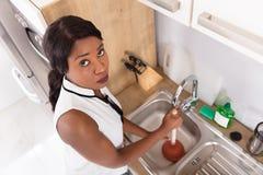 Несчастная женщина используя плунжер в закупоренной раковине стоковые изображения rf