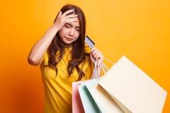 Несчастная молодая азиатская женщина с хозяйственными сумками и кредитной карточкой внутри стоковые фотографии rf