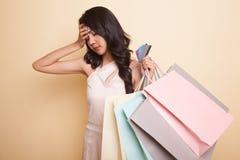 Несчастная молодая азиатская женщина с хозяйственными сумками и кредитной карточкой стоковое изображение