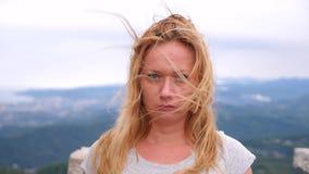 Несчастная молодая белокурая женщина стоя na górze горы на предпосылке облаков она смотрит уныло на камере _ сток-видео