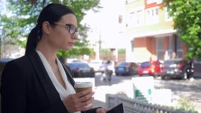 Несчастная молодая женщина использует устройство и выпивая кофе на улице думая о что-то акции видеоматериалы