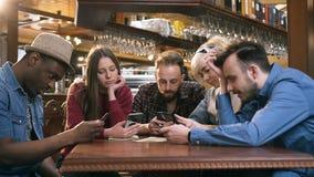 Несчастная, сверлильная группа в составе друзья используя умный телефон во время отдыхать в пабе, бар сток-видео