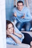 Несчастная унылая женщина покрывая ее уши Стоковые Изображения