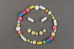 Несчастная улыбка созданная от покрашенных пилюлек МЕДИЦИНСКАЯ принципиальная схема Стоковая Фотография