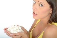 Несчастная Concerned молодая женщина держа пригорошню нездоровых кубов белого сахара Стоковое Фото