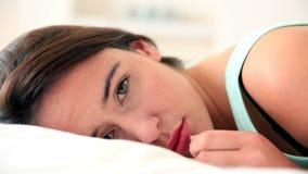 Несчастное брюнет лежа в кровати смотря камеру видеоматериал