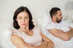 Несчастные пары имея конфликт в кровати дома Стоковая Фотография RF