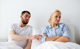 Несчастные пары имея конфликт в кровати дома Стоковая Фотография