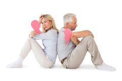Несчастные пары сидя держащ 2 половины разбитого сердца Стоковые Фото