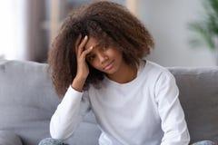 Несчастный Афро-американский девочка-подросток сидя самостоятельно, имеющ проблему стоковая фотография