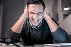 Несчастный безрадостный человек покрывая его уши с руками стоковые изображения