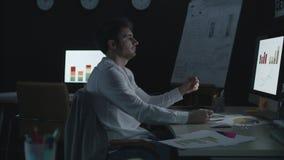 Несчастный бизнесмен анализируя диаграммы и диаграммы дела в офисе финансов видеоматериал