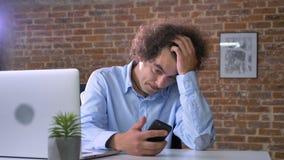 Несчастный бизнесмен имея затруднения с делом, работая на компьтер-книжке и держа телефон, сидя в современном офисе сток-видео