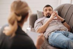 Несчастный бородатый человек смотря его психолог стоковая фотография rf
