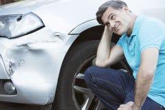 Несчастный водитель проверяя повреждение после автомобильной катастрофы Стоковые Изображения