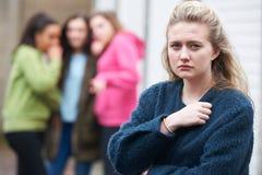 Несчастный девочка-подросток будучи поговоренным около пэрами стоковые изображения